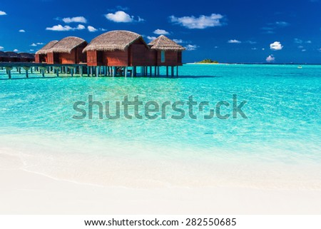 Overwater bungalow and white beach in blue lagoon of tropical Maldives - stock photo
