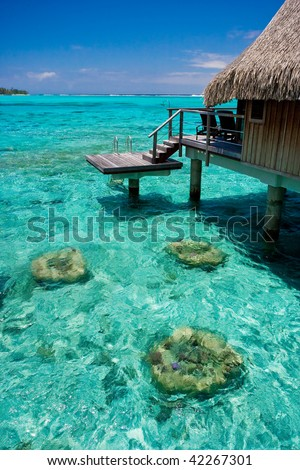 overwater bungalow tropical resort over turquoise coral reef water on exotic island - stock photo