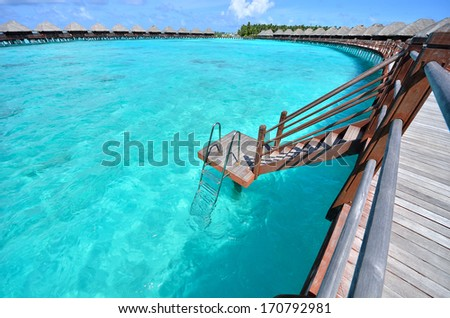 Overwater bungalow with steps into the green lagoon -- Maldives tropical island resort  - stock photo