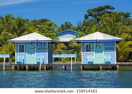 Overwater bungalows with palm trees in background, Bocas del Toro, Caribbean sea, Central America, Panama - stock photo