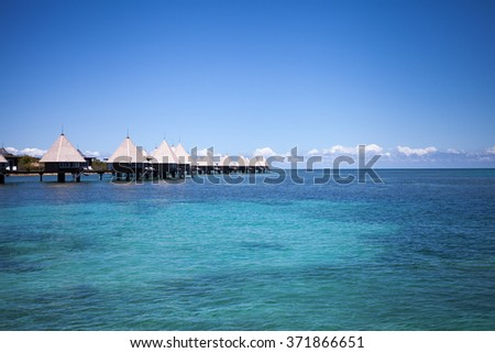 Overwater spa and bungalows in tropical blue lagoon - stock photo