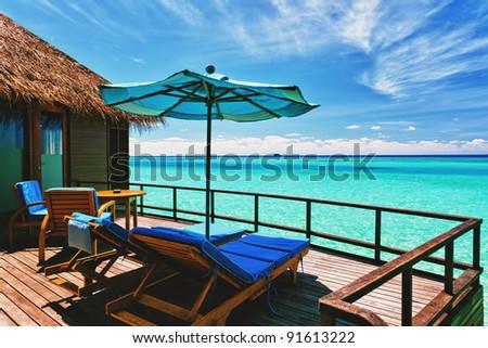 Overwater villa balcony overlooking green tropical lagoon - stock photo