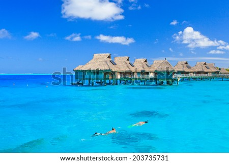 Overwater villas in blue tropical lagoon, Bora Bora, French Polynesia, South Pacific  - stock photo