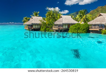 Overwater villas in tropical lagoon of Moorea Island with coral reef - stock photo