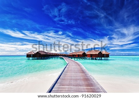 Overwater villas on the tropical lagoon - stock photo