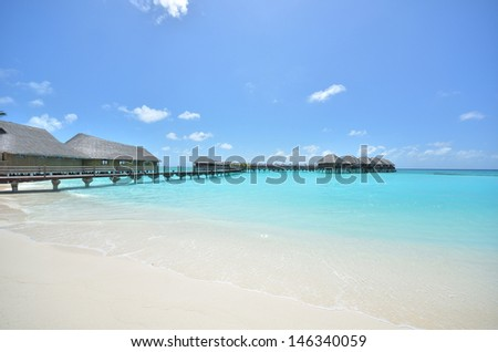 Overwater villas on the tropical lagoon -- maldives seascape - stock photo