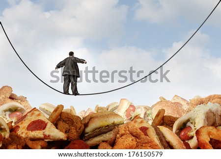 Overweight diet danger concept as an obese man walking on a tightrope high wire over greasy junk food as a metaphor for dieting risk and the challenges of eating disorders resulting in obesity. - stock photo