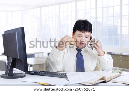 Overweight entrepreneur working on the table while eating and talking on the phone in office