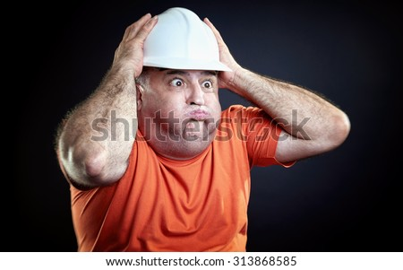 Overweight industrial worker gesturing hopeless. Hands over helmet, all over black background. - stock photo