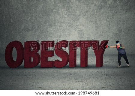 Overweight man exercise to lose weight by boxing and punching a big obesity text - stock photo