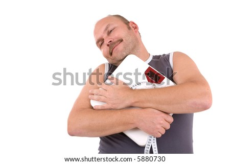 Overweight man hugging his weighing scale and measuring tape