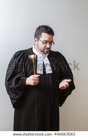 Overweight man in canadian lawyer toga, pounding a gavel in his hand - stock photo