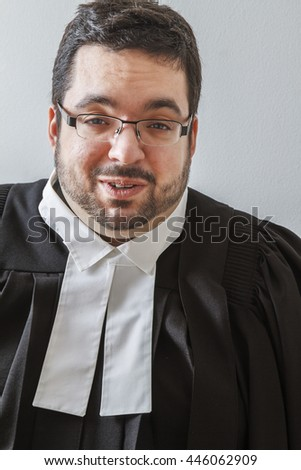 Overweight man in canadian lawyer toga, with happy expression, against a white background - stock photo