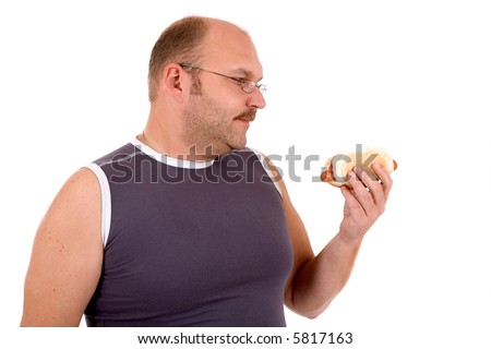 Overweight man looking at the hot dog in his hand - stock photo
