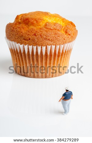 Overweight man looking up at an enormously large muffin a portion size or obesity concept - stock photo