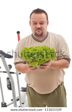 Overweight man not happy about his new diet based on fresh vegetables - weight loss concept - stock photo