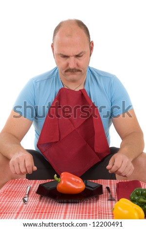 Overweight man sitting at the table with knife and fork and a pepper on his plate