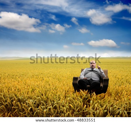 Overweight man sitting in an armchair in a green meadow - stock photo