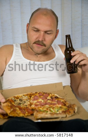 Overweight man sitting on the couch eating pizza and drinking beer - stock photo