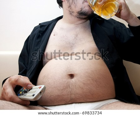 Overweight man sitting on the couch with a beer glass and remote control - stock photo