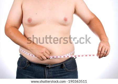 Overweight man uses a fabric tape to measure his waist size. - stock photo