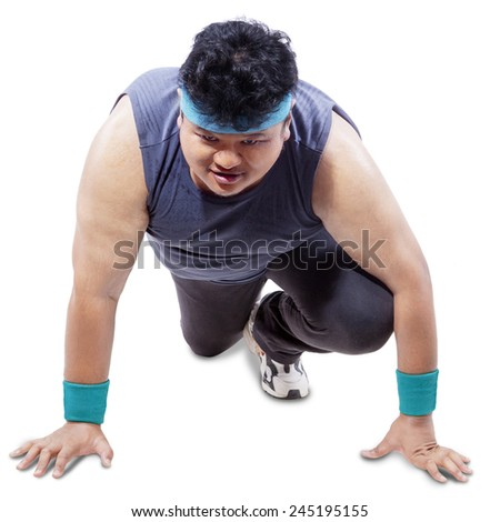 Overweight man wearing sports wear and ready to run, isolated on white background - stock photo