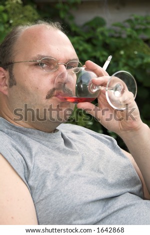 Overweight mature man sitting in a chair drinking too much and smoking too much - stock photo