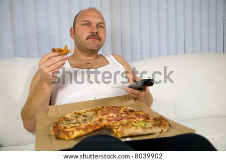 Overweight mature man sitting on the couch with a pizza and the remote control - stock photo
