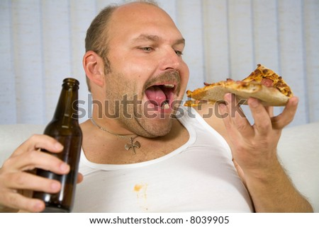 Overweight mature man with pizza in one hand and a beer in the other - stock photo
