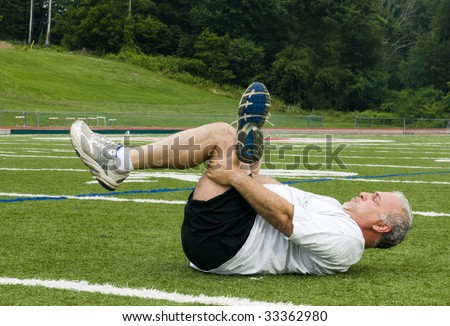overweight middle age senior man stretching his muscles after exercising on sports field - stock photo
