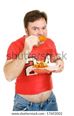Overweight middle aged man in tight football jersey, chowing down on fried chicken wings.  Isolated on white.