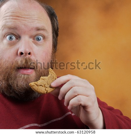 Overweight middle aged man with cookies - stock photo