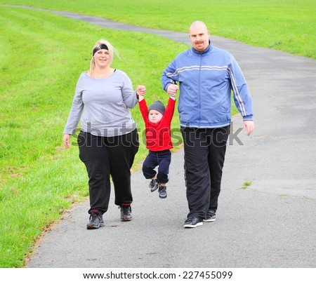 Overweight parents with her son walking together. - stock photo