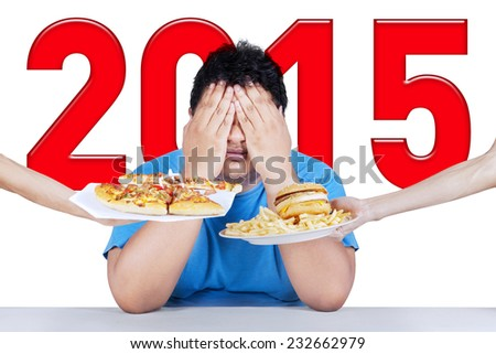 Overweight person closing his face from junk food, symbolizing his plan for a healthy life in 2015 - stock photo