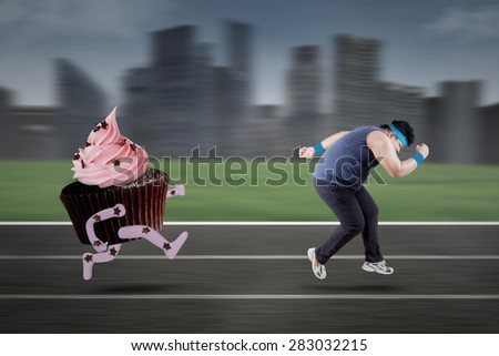 Overweight person exercising on track to lose weight and hallucinate chased by cupcake - stock photo