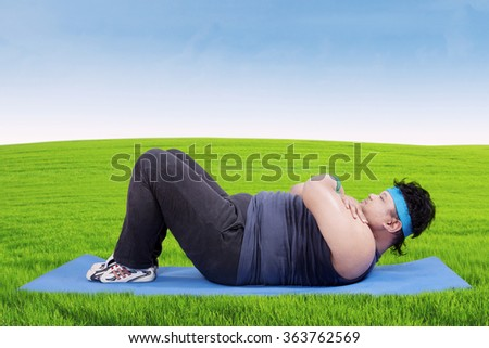 Overweight person lying on the mattress while wearing sportswear and doing exercise on the meadow - stock photo