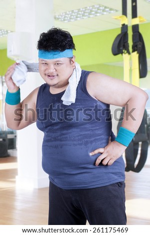 Overweight person smiling at the camera while wiping his sweat with a towel at fitness center - stock photo