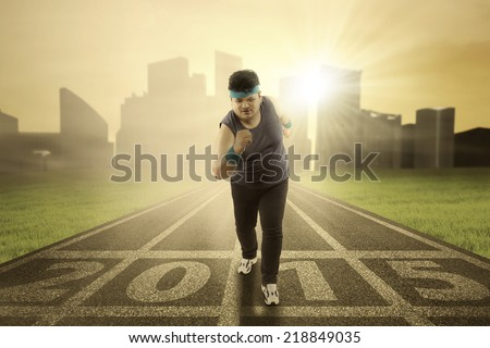 Overweight person wearing sportswear and run on track with number 2015 - stock photo