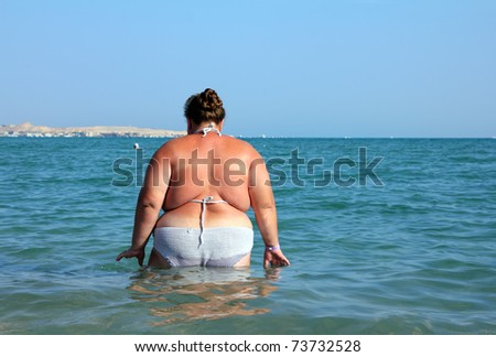 overweight woman bath in sea - rear view - stock photo