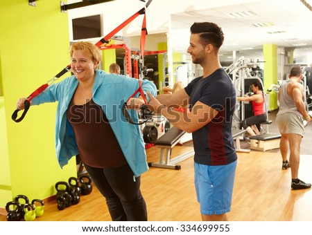 Overweight woman doing suspension training with the guidance of personal trainer. - stock photo