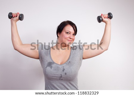 Overweight woman exercising, lifting weights - stock photo