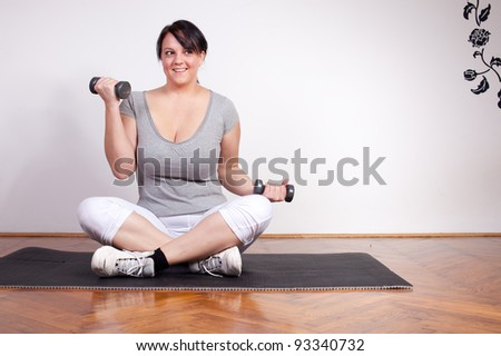 Overweight woman exercising, lifting weights at home - stock photo