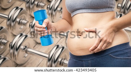overweight woman hand holding fat belly and dumbbell - stock photo