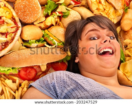 Overweight woman holding hamburger. - stock photo