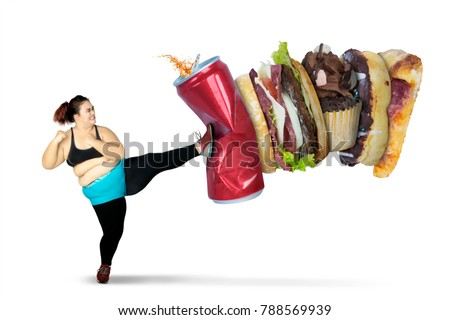 Overweight woman kicking soft drink and fast foods while wearing sportswear, isolated on white background