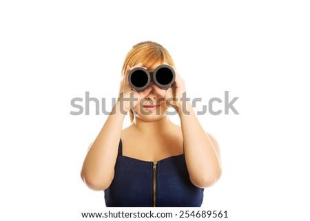 Overweight woman looking through binoculars. - stock photo