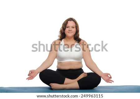 overweight woman practices yoga on blue mat - stock photo