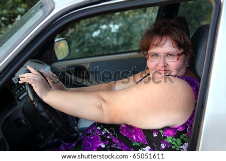 overweight woman sitting behind the wheel of car - stock photo