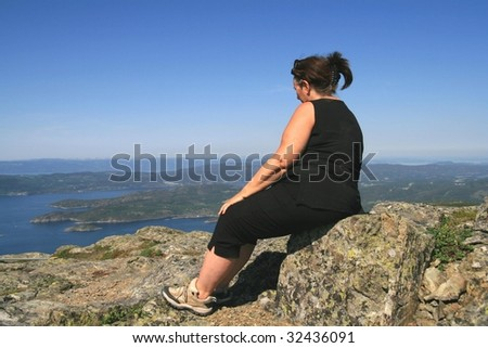 Overweight woman sitting on a mountain - stock photo