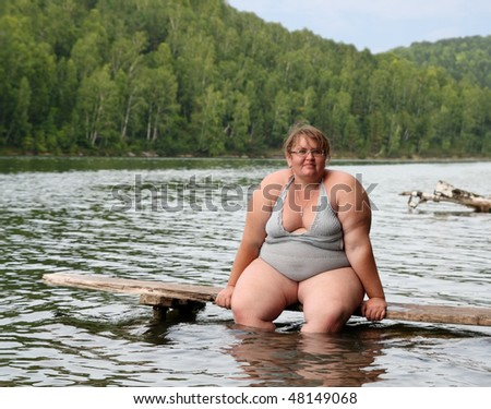 overweight woman sitting on stage in lake - stock photo